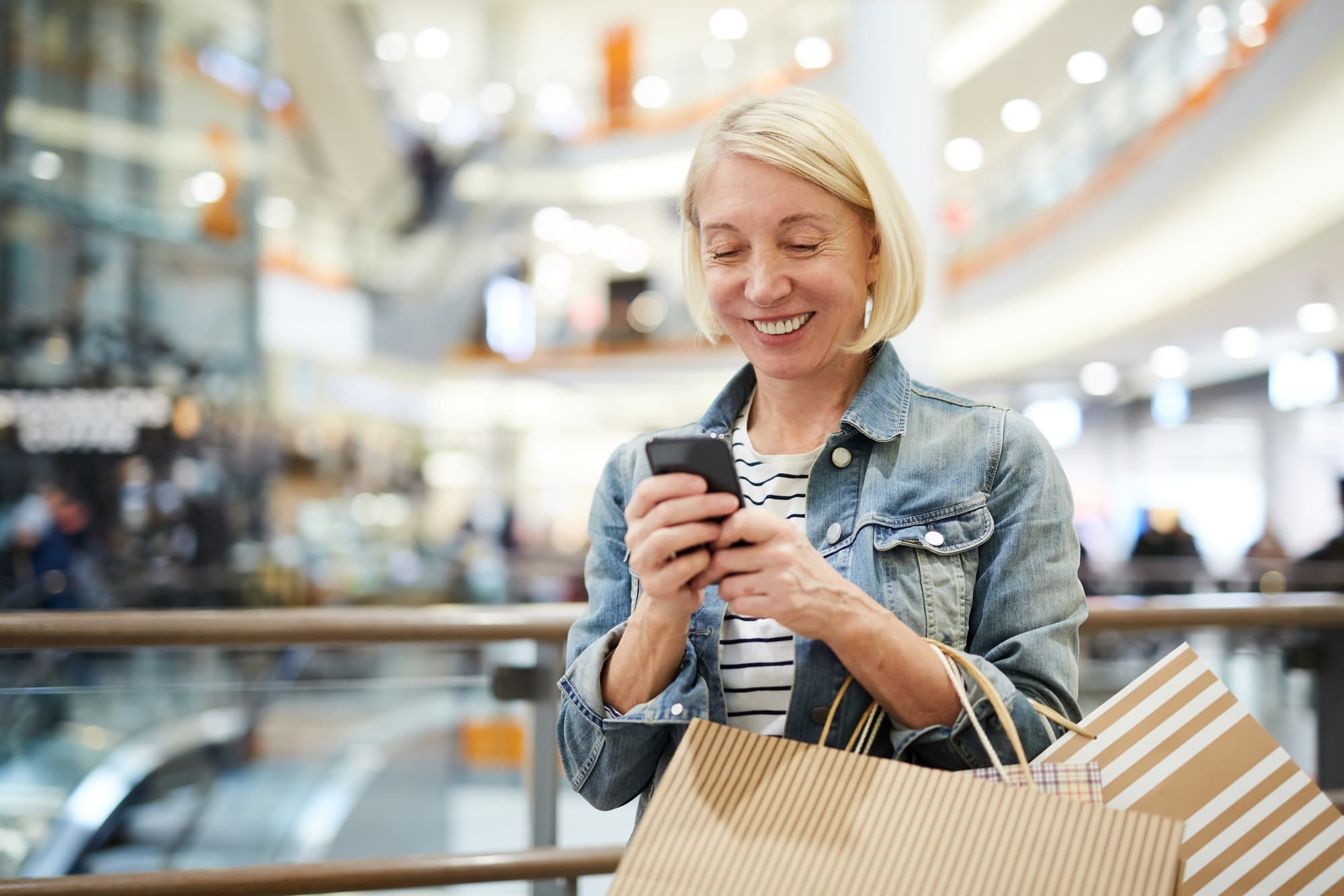 Happy woman texting sms in shopping mall