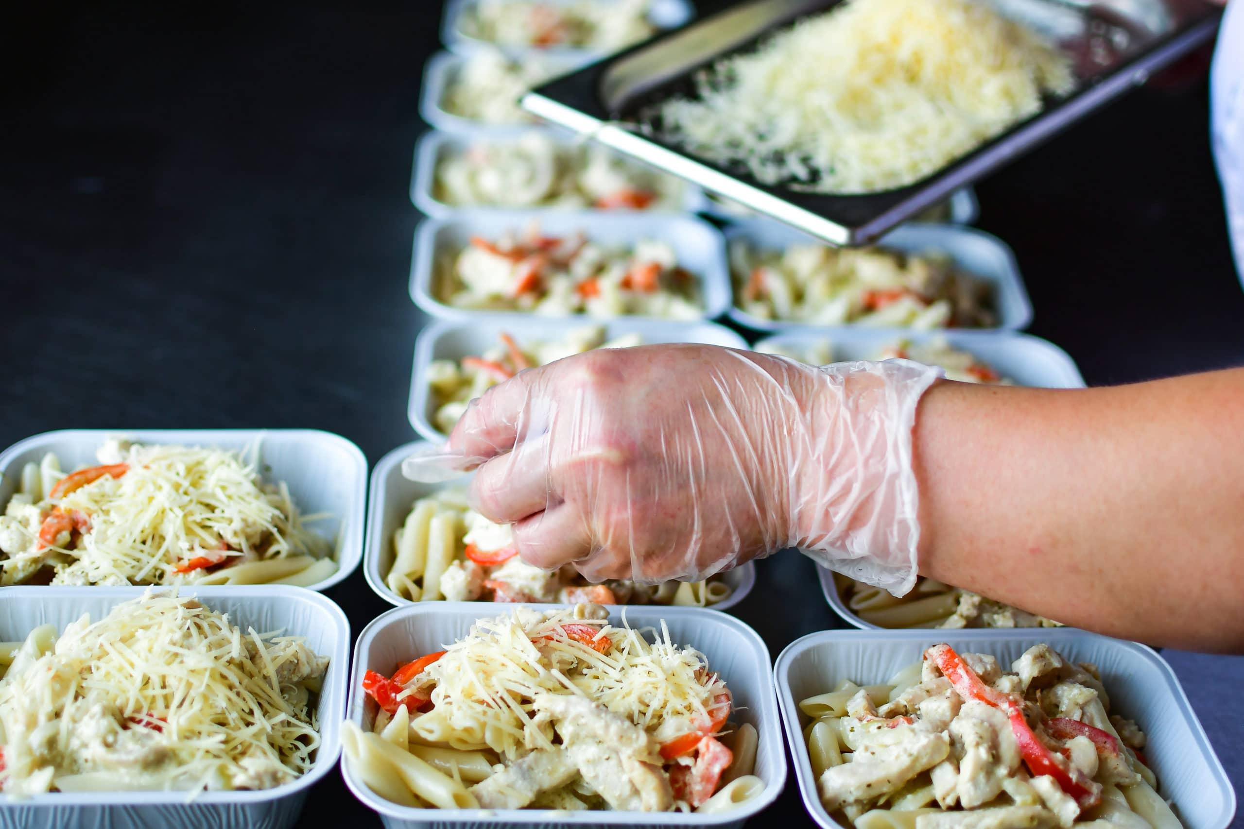 Hand preparing large order of take out pasta